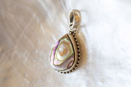 Sterling silver pendant on white mother pearl background Stock Photo