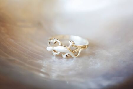Sterling silver ring in shape of lizard on white shell background