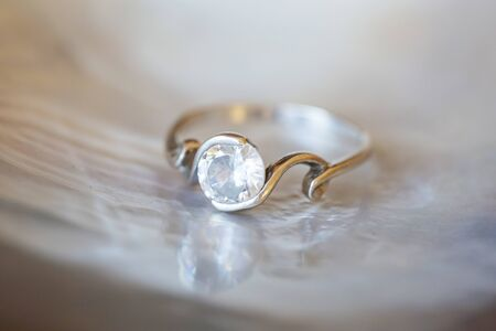 Sterling silver ring with zircone stone on pearl shell white background 写真素材