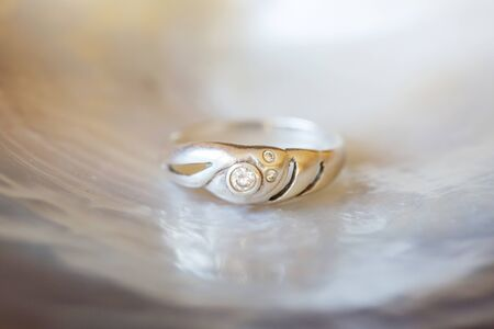 Sterling silver ring with zircone stone on pearl shell white background