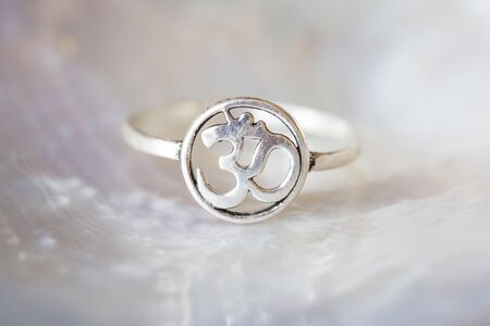 Silver ring tiny jewelry piece on white pearl background in the shape of om