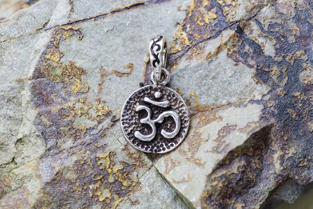 sterling silver metal pendant on natural background in the shape of om 写真素材
