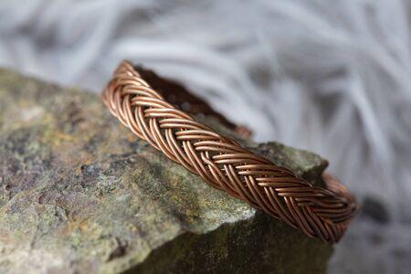 Copper metal wire elegant bracelet on rocky background