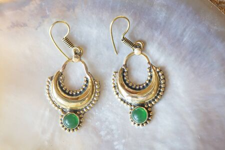 Brass pair of earrings in oriental style on white shell background