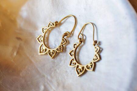 Brass pair of earrings in oriental style on white shell background Stock fotó - 147451341