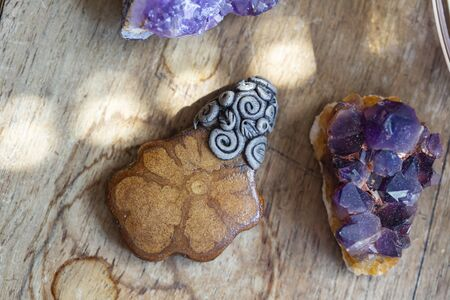 Beautiful ayhuasca root pendant on wooden backround with amethyst druses Stock fotó