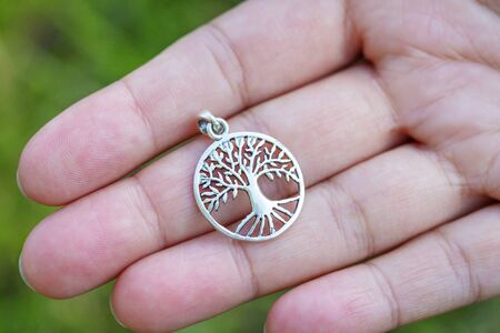 Sterling silver pendant in the shape of tree on female hand
