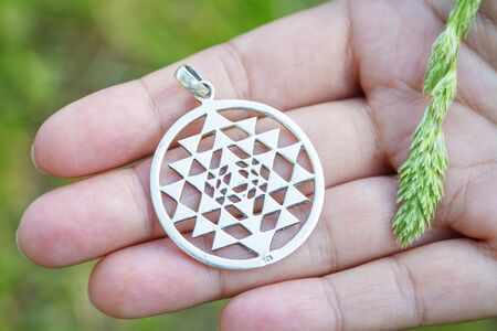 Sterling silver pendant in the shape of sri yantra sacred geometry on female hand
