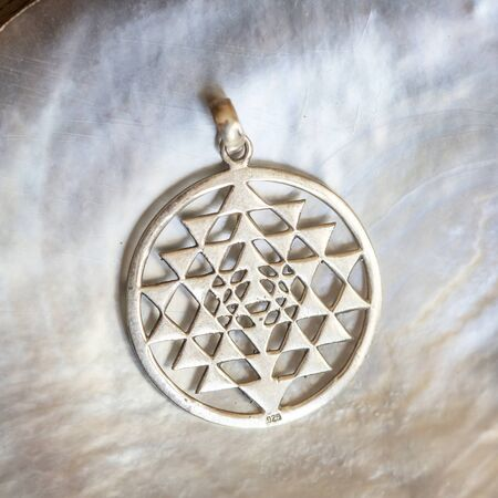 Sterling siver pendant in the shape of sacred geometry sri yantra on white shell background Stock fotó
