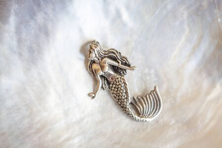 Sterling siver pendant in the shape of mermaid on white shell background Stock fotó