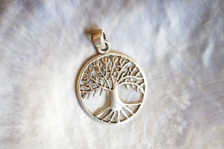 Sterling siver pendant in the shape of the tree on white shell background