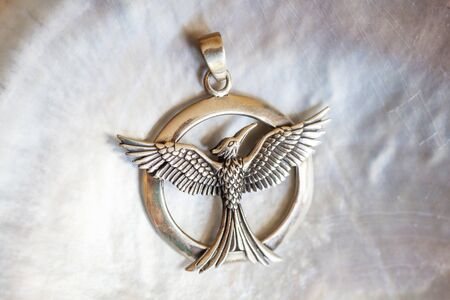 Sterling siver pendant in the shape of phoenix on white shell background