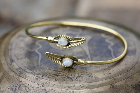 brass bracelet with moon stone decoration in the shape of feather Foto de archivo