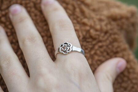 Female hand wearing silver metal ring in the shape of om