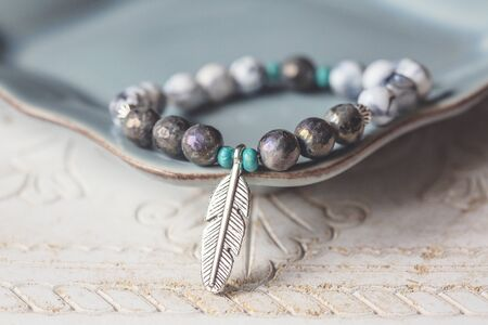 Electroplated fazeted labradorite mineral stone beads bracelet with feather pendant Stock Photo
