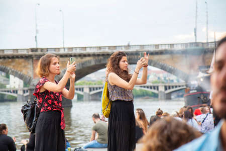 Prague, Czech republic, June 13, 2020: Prague Vltava waterfront, people enjoying sunset time at the quay, young girls taking cellphone picture of new restaurant design Sajtókép