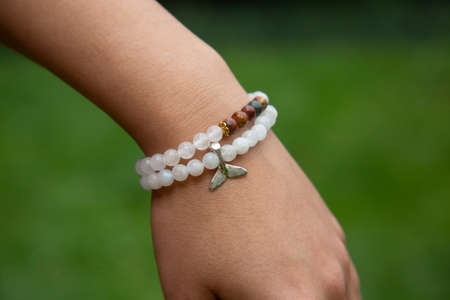 Outdoor detail of female hand wearing mineral crystals round beads bracelet