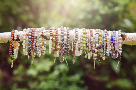 Collection of crystals mineral stone beads yoga bracelets hanging on the branch on natural green bokeh background