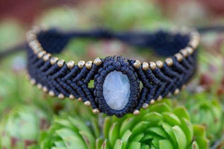 Boho bracelet with mineral stone in macrame technique on houseleek plant