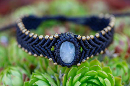 Boho bracelet with mineral stone in macrame technique on houseleek plant