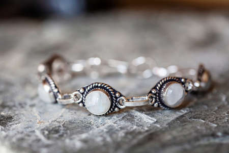 Beautiful female bracelet with moon stone on neutral rocky background