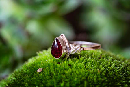 Sterling silver ring with garnet gemstone on green moss background