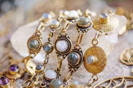 Brass jewelry with natural mineral gemstones on natural rocky background