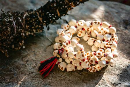 White stone skull beads necklace mala on rocky background