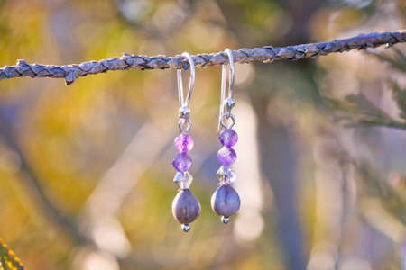 Faceted mineral stone beads romantic style earring hanging on natural background Stock fotó