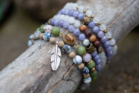 collection of tiny mineral stones bracelets on wooden stick natural background