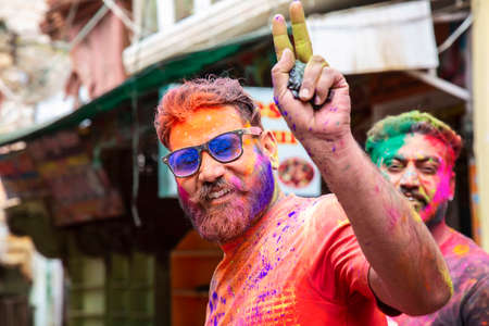Pushkar in Rajasthan, India, 10th of March 2020: People celebrating Holi festival throwing colors and dancing on the street