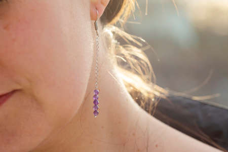 Female ear wearing long amethyst mineral stone earring