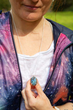 Girl chest detail in space jacket with labradorite pendant on silver chain 版權商用圖片