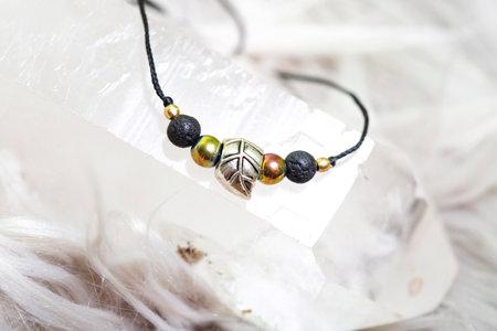 Fashionable mineral bead bracelet on black string on bright natural background Stock fotó