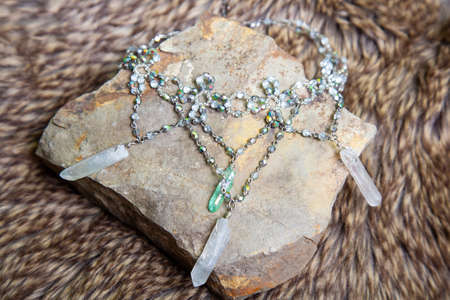 Crystal quartz romantic princess necklace from fairytale on rocky stone background
