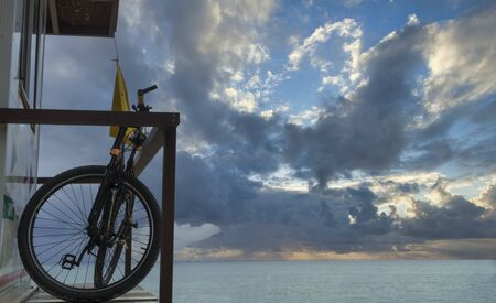 Sunrise on the beach with a bicycle; the lifeguard cottage with a bicycle and yellow flag at a beach in Playa del Carmen, Mexico. In the background the Caribbean sea and the cloudy sky