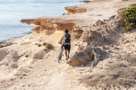 An unknown tourist walks with his backpack along a path overlooking the sea with his bicycle. Formentera island, Mediterranean sea, Spain