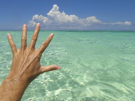 Woman saluting with open hand a tropical beach. Hand of a white woman greets the sea water. Caribbean Sea, Mexico