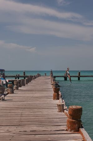 A lovers couple jump into the sea from the pier, Caribbean ocean, Mexico, Cancun