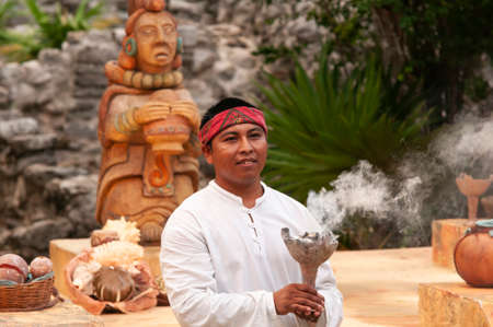 Young Mayan man with a burning brazier in his hand during a local ceremony - red bandana on the forehead - indigenous decorations on the background, Yucatan, Mexico