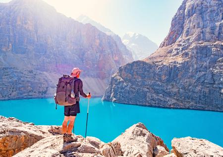 Man with backpack near lake Big Alo on rocky mountain background. Fann Mountains, Tajikistan, Central Asia