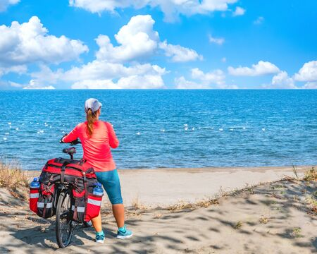 Young woman tourist on a mountain bike with a big backpack traveling on the seaside of Black Sea in Bulgaria Banco de Imagens
