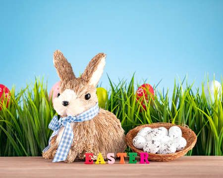 Easter eggs and cute bunny on wood table with green grass. Festive decoration