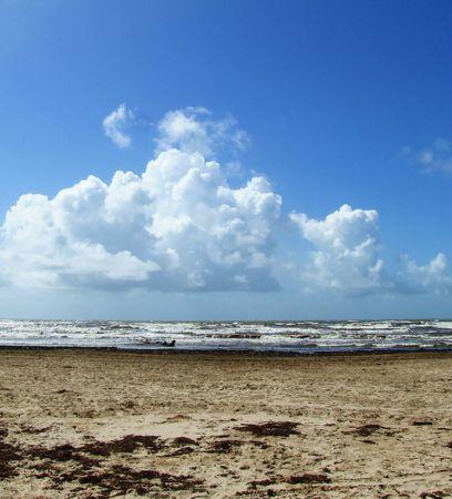 Clouds, sky, surf, and beach meet the horizon