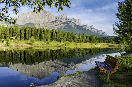 canmore: Looking North West at Quarry Lake in Canmore Alberta, beautiful reflection of Mount Rundle , bench in foreground stock photo