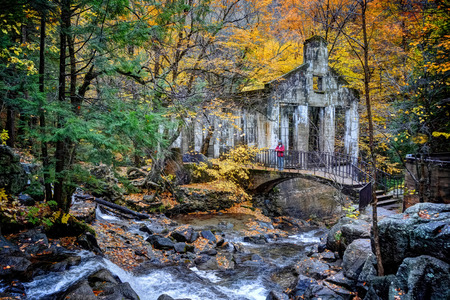 carbide: Shot of  ruins and waterfall with woman standing on bridge