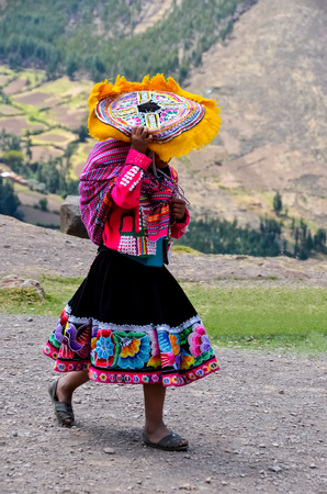 Woman walking in traditional clothes in Pisac, Peru