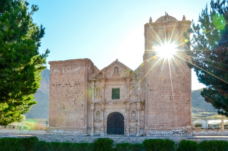 Facade view of Pupuka church with sunburst through bell tower, Pukara Peru