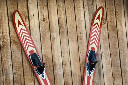 A pair of water skis hung on a board wall and nailed, attached to the nail, a pair of water skis hung and nailed to a board wall 版權商用圖片