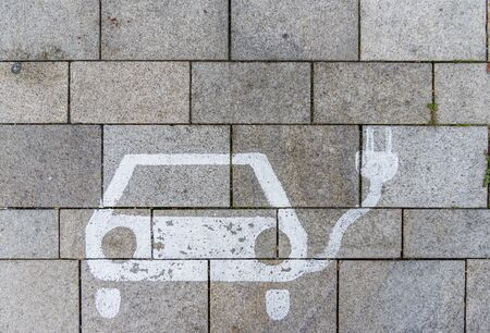 Sign for charging station on parking lot with concrete pavement